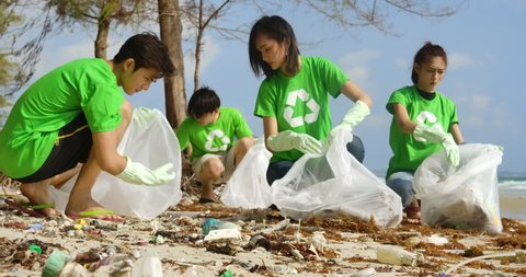 Group of young asian people volunteers in green t-shirts cleaning up the beach with plastic bags full of garbage. Safe ecology concept. 4k resolution.
