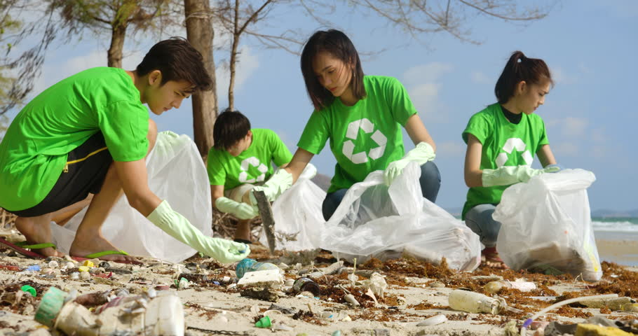 Group of young asian people volunteers in green t-shirts cleaning up the beach with plastic bags full of garbage. Safe ecology concept. 4k resolution. | Shutterstock HD Video #1026301064