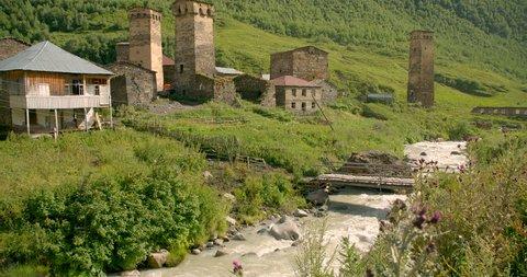 Pan up wide of the stone medieval fortified Svaneti tower houses of  Ushguli, Upper Svaneti, Samegrelo-Zemo Svaneti, Mestia, Georgia.