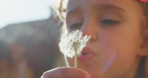 Authentic shot of cute little girl carefree blowing a dandelion outside her house on a sunny day.