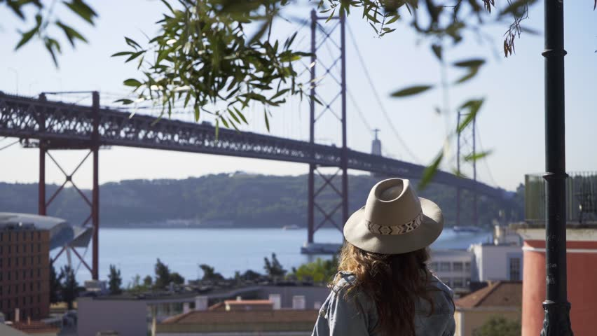 Young casual girl in hat sitting on view point above Lisbon, smiling and enjoying beautiful cityscape against famous 25th april bridge in sunlight | Shutterstock HD Video #1026348464