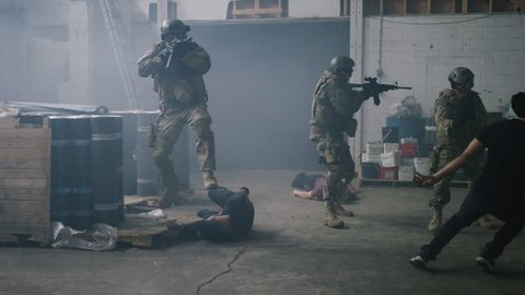 Three special ops military SWAT team members appear from dark smoke filled warehouse walking towards camera taking out bad guys in warehouse under dramatic daytime lighting. Wide shot on RED camera