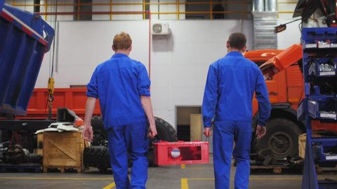 workers in uniform carry large accumulator battery along repair workshop slow motion backside view