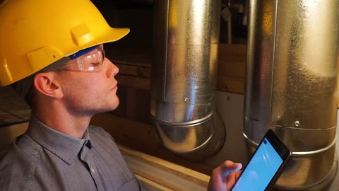 Young white man wearing a safety hard hat and safety glasses going a home inspection with a tablet