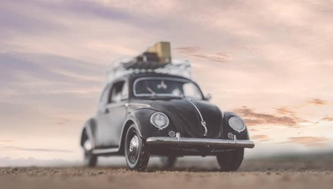 NITRA, SLOVAKIA - JUNE 28 2018: Volkswagen Beetle with suitcases on the roof by sunset. Sunset over Volkswagen Beetle. Classic car VW Beetle by summer sunset.
