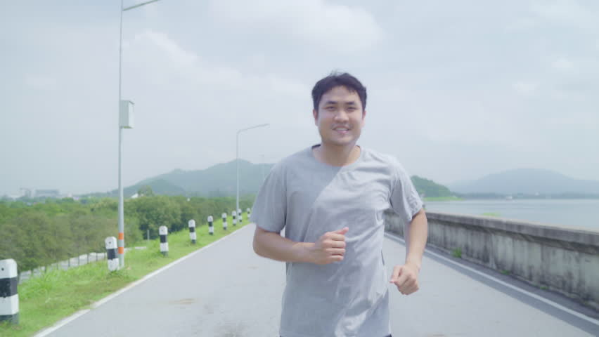 Asian runner man running and jogging on street, Healthy handsome young sporty male exercise near lake. Lifestyle fit and active men exercise on street concept. #1026476984