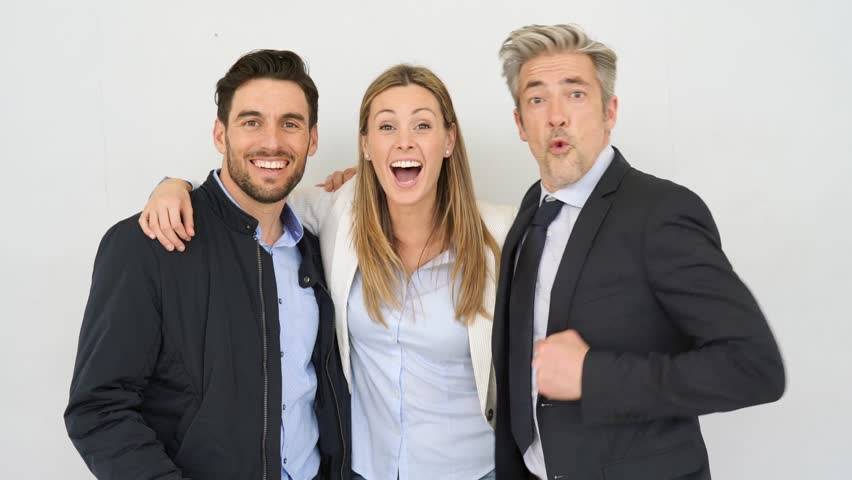 Dynamic coworkers looking at camera celebrating on grey background | Shutterstock HD Video #1026498524