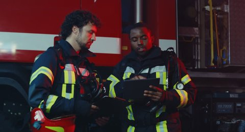 Mixed races men firemen standing at the fire truck and talking while using tablet device and some documents, then they female colleague coming and discussing something with them.