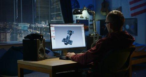 Medium shot of a man using a computer to design a hinge at home