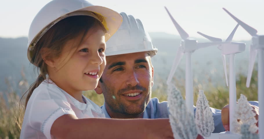 A father engineer shows his project to his daughter for the construction of a wind farm. The daughter is interested in renewable energy. Concept of: family, engineering, future love for nature.