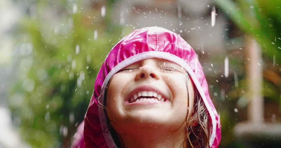 A happy girl is playing in the rain and is happy because she has fun.  #1026703814