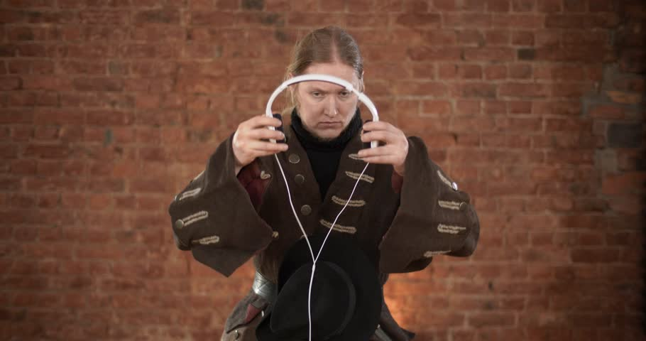 Serious 19th-century military man putting on headphones and listening to music standing isolated on brick wall background   Shutterstock HD Video #1026704144