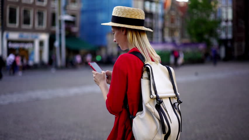 Slow motion of millennial female tourist with backpack messaging with people on travel blog using 4g internet connection outdoors in city.Hipster girl taking photo for share media in social network