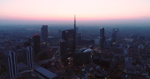 Milan, Italy - March 31, 2019: Milan city skyline at dawn, aerial view, flying over financial area skyscrapers in Porta Nuova district. Unicredit Tower office building at sunrise.