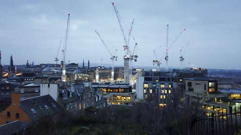 Early morning timelapse of Edinburgh as dawn breaks over the city, showing large construction cranes working and traffic making its way through the streets