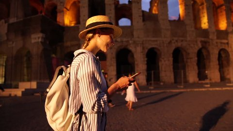 Smiling female traveler with backpack walking near coliseum using app with navigation for planning route in Rome satisfied with roaming internet. Cheerful hipster girl using smartphone