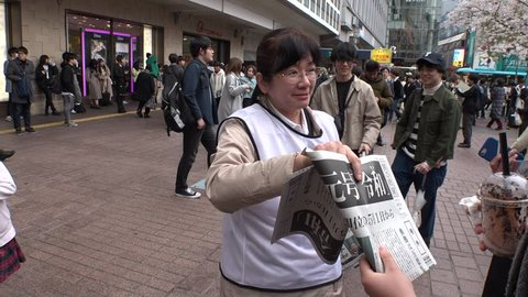 "SHIBUYA,  TOKYO,  JAPAN - CIRCA APRIL 1st 2019 : ""REIWA"" becomes the new name, for a new era, under a new Emperor.  People try to receive a copy of Asahi newspaper reporting the name of new era."