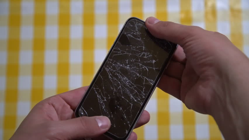 Concept of smart phone with broken screen. Top view of man hands holding a phone with cracked display. Cracked, shattered lcd touch screen on modern cellphone. Gadget needs repairing  | Shutterstock HD Video #1026774554