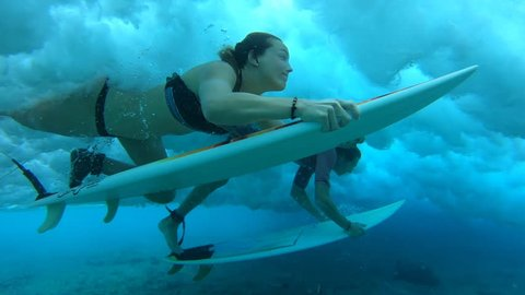 Two young surfers make dive with their surfboards to safely pass the ocean wave