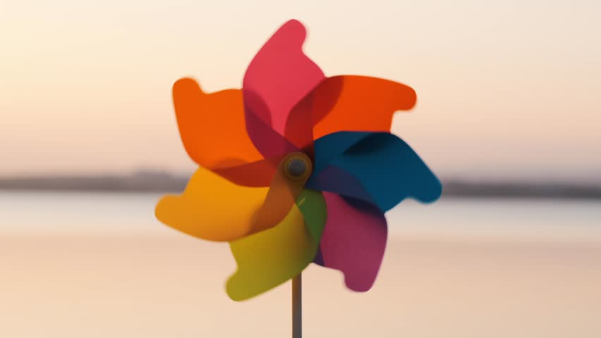 A rotate colored plastic pinwheel with a blowing wind stands on sand by the sea against the smooth surface of the sea and a bright pink sunset. Toy mill on the beach. Large disk of the sun. Copyspace | Shutterstock HD Video #1026840194