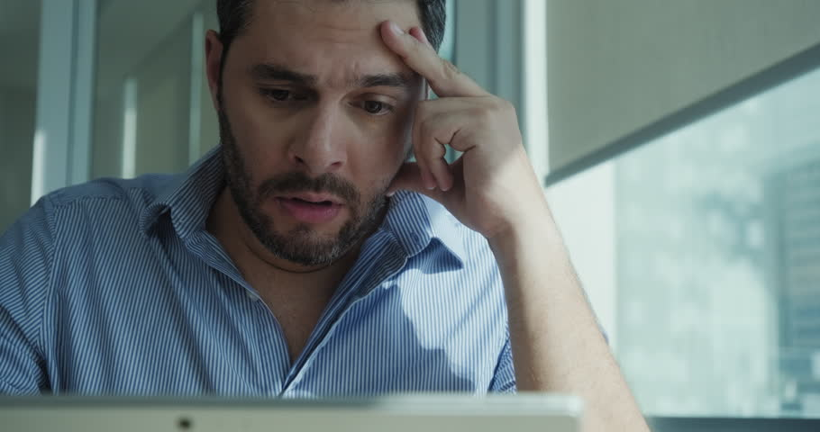 Angry businessman working with laptop computer in office, losing patience. Impatient business man under stress at work with pc. Young latin manager worried for technology problems and software virus