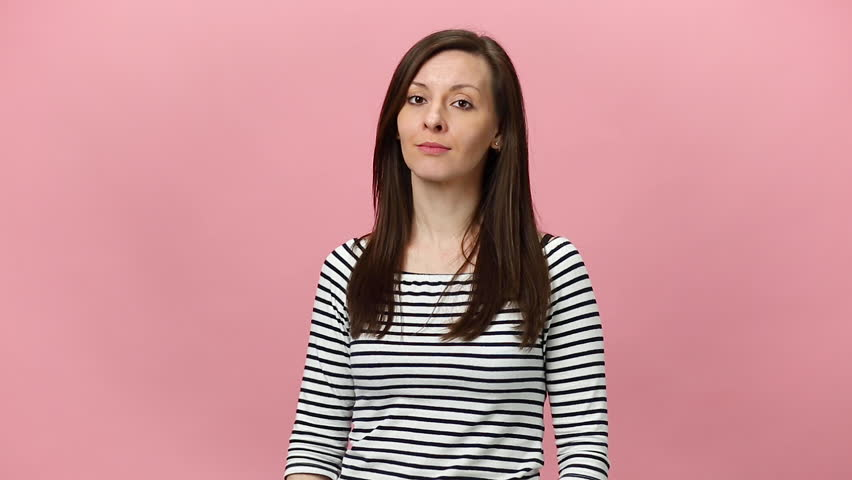 Smiling young woman in striped shirt looking at camera rubbing fingers showing cash gesture asking for money isolated over pastel pink background in studio. People sincere emotions, lifestyle concept.   Shutterstock HD Video #1026856844