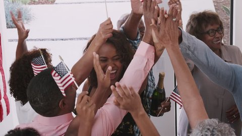 African American family celebrating Independence Day high five with their relatives, close up, elevated view
