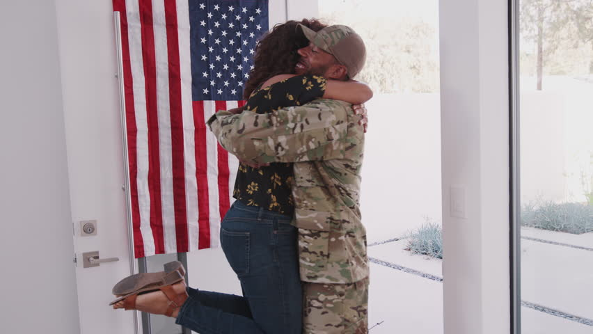 Young African American woman running to the front door and welcoming home her soldier husband
