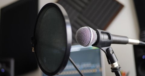 A vocal microphone and pop filter for singing or recording a podcast in a bedroom music studio SLIDE LEFT.