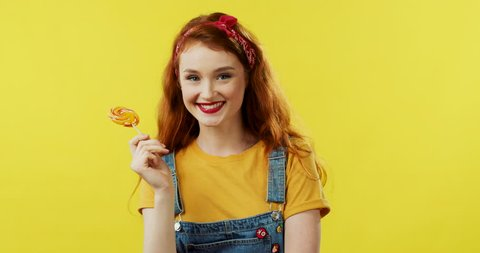 Portrait shot of the young Caucasian pretty girl with red hair standing on the yellow screen background, holding a lollipop and smiling joyfully. Close up.
