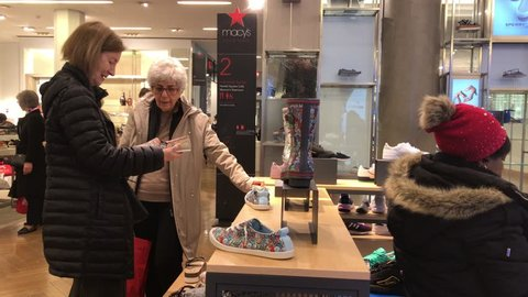 New York , April 5, 2019: Two elderly women are shoe shopping at Macy's department store.