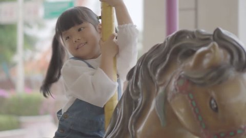Asian child cute or kid girl enjoy smiling and happy fun with riding horse or playing carousel in amusement park on summer holiday relax and family vacation on slow