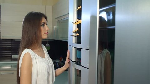 Close-up girl takes a note from the refrigerator door. Slow motion. Woman writing message on note stuck to refrigerator door at home. Woman holding empty note near refrigerator door in kitchen.