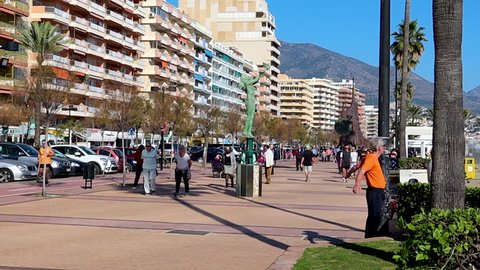 FUENGIROLA, SPAIN - APRIL 7, 2019: People and tourist walking on famous Paseo Maritimo promenade, elder man working out