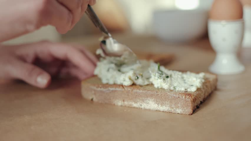 Female chef putting cheese spread on a toasted whole wheat bread 4k | Shutterstock HD Video #1027142474