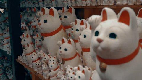 Hundreds of Japanese Maneki-Neko (lucky cat) statues arranged at the Gotokuji Shrine in Tokyo, Japan.