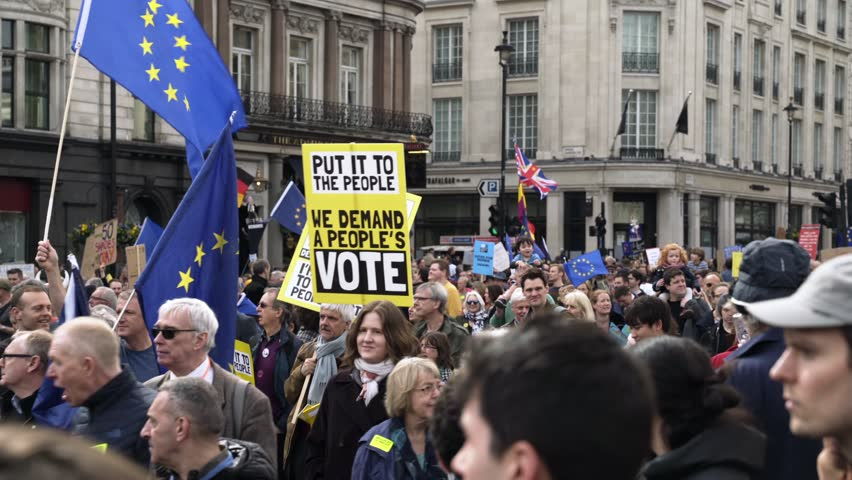 LONDON, UK - MARCH 23 2019: Thousands of pro EU protesters against Brexit at The Peoples Vote demonstration walks with placards and European Union flags