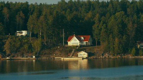 Big house in the Nordic coast with a small boathouse and a pier. Cinematic drone shot.