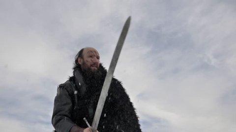Portrait of bearded medieval scandinavian warrior killing his enemy with sword