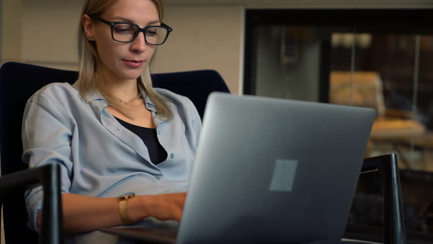 Caucasian female remote worker sharing media files via bluetooth connection on digital tablet and laptop computer connected to internet for browsing internet websites. Young woman using technology