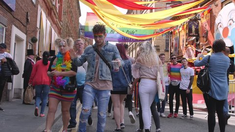 Dancing guy at LGBTQ, Lesbian, Gay, Bisexual, Transgendered, Queer, Pride Parade Street Party Celebration with Rainbow flags in slow motion Full Body