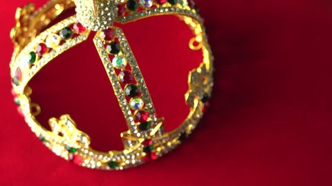 Gold crown with luxury color jewels and diamonds, view from above. With reflection and lights sparks. Slow rotation on the red royal color surface. 4k, uhd.