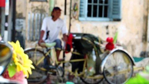 PENANG, MALAYSIA, NOV 14 2017, The malaysian driver of rickshaw waits on the street for the passenger