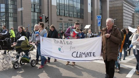Brussels, Belgium - March 30, 2019:Cheerful view of a group of green peace people walking with prams and kids in them and keeping a banner Babies for peace in a street in Belgium