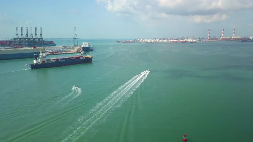 Aerial shot of small boat & container ship leaving container port, Singapore