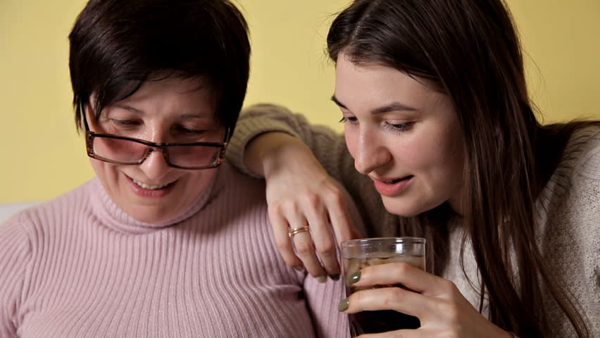 Mother and daughter sitting at home on the couch. The use of smartphones, browsing, reading the news. Drink Coca-Cola, whiskey | Shutterstock HD Video #1027324664
