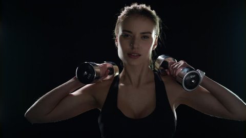 Fitness woman training dumbbell exercise on black background. Sport model workout with dumbbells in gym. Fit girl lifting dumbbell in slow motion. Yound woman training body