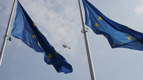 Wonderful view of the European Union flag waving in a light blue and cloudy sky with a flying police helicopter in Brussels in slow motion