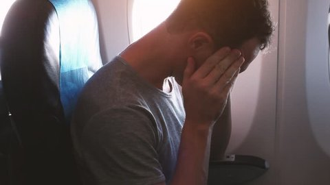 headache in the airplane, man passenger afraid and feeling bad and sick during the flight in plane, aerophobia