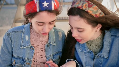 Two nice girl friends hanging out at stairs, using mobile phone sending text message Snapchat sharing digital content on social media enjoying free time, dressed jeans jacket and colourful headbands